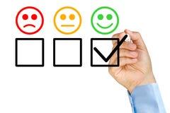 Mão que põe o formulário de avaliação do serviço ao cliente da verificação foto de stock
