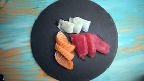 Mão que põe o sashimi sobre uma placa da ardósia filme