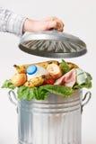 Mão que põe a tampa sobre a lata de lixo completamente do alimento Waste Fotografia de Stock