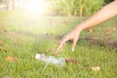 Mão que pegara a limpeza de garrafa plástica no parque imagens de stock royalty free