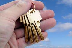 Mão que prende a chave dourada imagem de stock