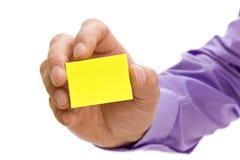 Mão que prende a nota de post-it em branco Fotografia de Stock