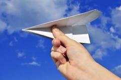 Mão que prende o avião de papel imagem de stock