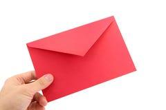 Mão que prende o envelope vermelho fotografia de stock