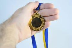 Mão que prende o troféu dourado bonito (da medalha) imagem de stock