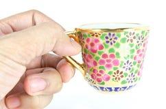 Mão que prende um copo de chá tailandês dourado Foto de Stock Royalty Free