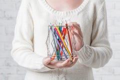 Mão que prende um estanho com lápis da cor Imagens de Stock