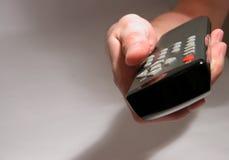 Mão que prende um telecontrole imagens de stock