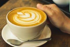 Mão que prende uma chávena de café Imagens de Stock