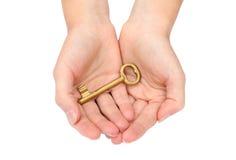 Mão que prende uma chave do ouro Imagens de Stock Royalty Free