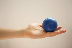 Mão que prende uma esfera do esforço Imagens de Stock Royalty Free