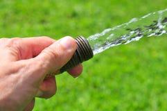 Mão que prende uma mangueira da água Imagem de Stock
