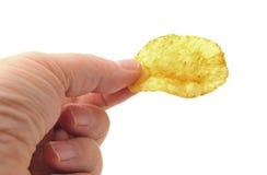 Mão que prende uma microplaqueta de batata Fotografia de Stock