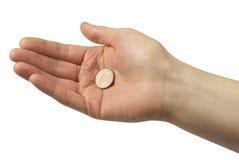 Mão que prende uma moeda de um centavo