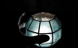 Mão que prende uma vela azul Imagens de Stock