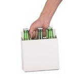 Mão que prende uns seis blocos de frascos de cerveja Fotografia de Stock Royalty Free