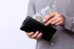Mão que puxa 100 dólares de cédulas Fotografia de Stock Royalty Free