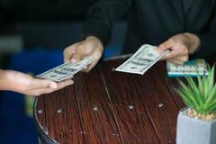 Mão que recebe o dinheiro, dólares americanos, do homem de negócio, homem de negócios que dá o dinheiro a seu sócio ao fazer o co fotografia de stock