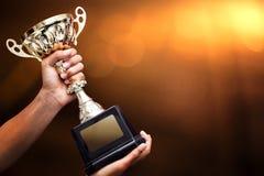 Mão que sustenta um troféu do ouro imagem de stock