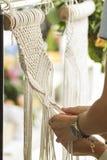 Mão que tece a tapeçaria bege do macramê do fio fotografia de stock royalty free