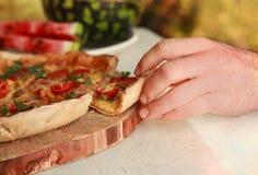Mão que toma a única fatia de pizza italiana Fotografia de Stock