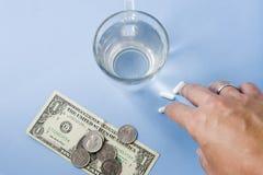 Mão que toma comprimidos Dinheiro e moedas com comprimidos e um vidro do fre fotos de stock
