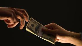 Mão que toma dólares no fundo preto, conceito do dinheiro sujo, pagamento para o crime vídeos de arquivo