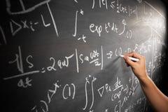 Mão que trabalha na equação imagem de stock
