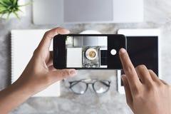 A mão que usa o telefone toma a imagem na mesa do trabalho Fotos de Stock