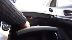 A mão remove um pano vermelho da parte inferior do compartimento de luva do carro video estoque