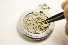A mão repara o relógio mecânico no fundo branco Fotografia de Stock Royalty Free