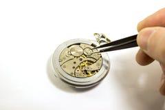 A mão repara um relógio mecânico velho Imagem de Stock Royalty Free