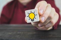 A mão selecionou cubos de madeira com símbolo amarelo da ampola na tabela de madeira Ideia nova, conceitos da inovação e soluções foto de stock royalty free
