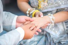 Mão tailandesa do ` s do noivo que põe uma aliança de casamento sobre o dedo do ` s da noiva Fotos de Stock Royalty Free
