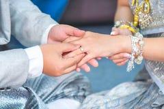 Mão tailandesa do ` s do noivo que põe uma aliança de casamento sobre o dedo do ` s da noiva Imagem de Stock