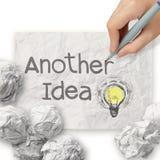 A mão tira uma outra ideia que a ampola com recicla o envelope Imagem de Stock