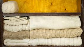 A mão toma as bolas das lãs, agulhas de confecção de malhas, telas de lã das prateleiras filme