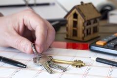 A mão toma as chaves da casa em um fundo Fotos de Stock