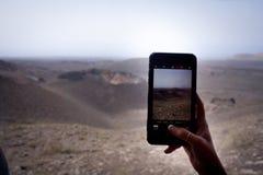 A mão toma um smartphone do whit das imagens no parque do timanfaya imagens de stock royalty free