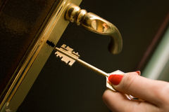 Mão, travando uma chave uma porta do ferro Imagens de Stock