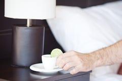 Mão, um copo do chá na tabela de cabeceira e lâmpada Fotografia de Stock