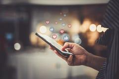 Mão usando o smartphone com conceito social dos meios fotos de stock