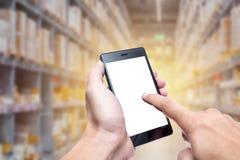 Mão usando o smartphone com tecnologia da gestão de inventário do armazém fotos de stock royalty free