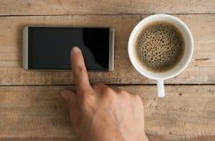 Mão usando o smartphone na madeira Imagem de Stock