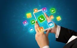 Mão usando o telefone com ícones brilhantes da aplicação Foto de Stock
