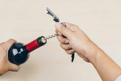 Mão usando um corkscrew do metal imagens de stock