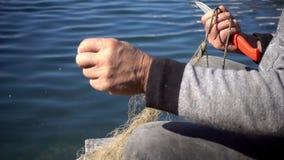 Mão velha do pescador que repara a rede de pesca video estoque