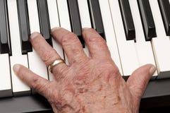 Mão velha em chaves do piano Fotografia de Stock Royalty Free