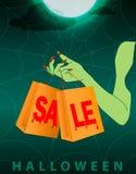 Mão verde da bruxa que guarda dois sacos de compras do oringe com venda vermelha ensanguentado do texto no fundo escuro da noite  ilustração royalty free