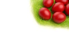 Mão vermelha ovo da páscoa tingido na grama falsificada. Fotos de Stock Royalty Free